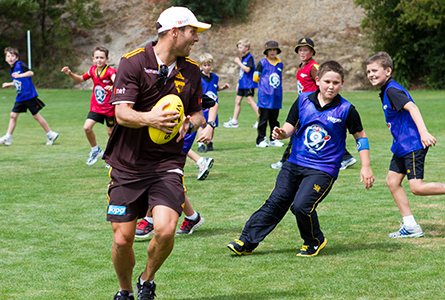 Hawthorn player Brad Sewell tries to keep the ball away from Hutchins Junior School students.