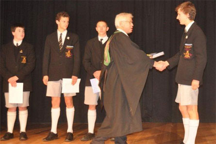 Henry West receives his Geography Competition Prize from Acting Headmaster Barrie Irons at the Headmaster's Assembly.