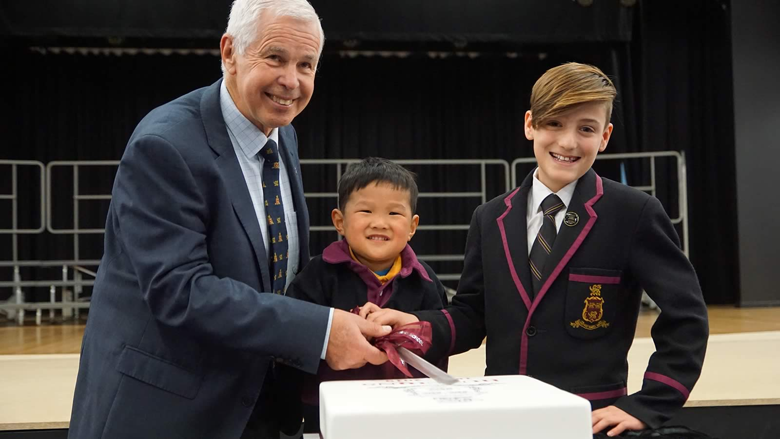 President of the Hutchins School Old Boys' Association Mr Barrie Irons, Elliott Lee (Pre-Kindergarten) and Thomas Birkett (Year 6) cutting the Anniversary Cake.